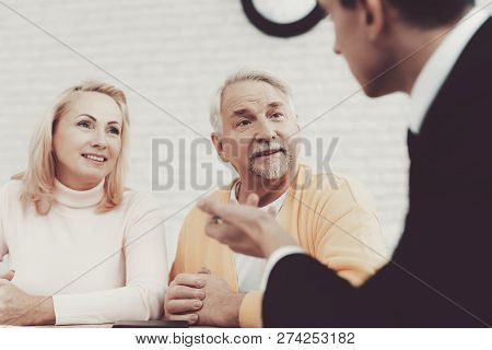 Old Man And Woman Visiting Young Lawyer In Office. Important Documents. Modern Law Office. Grandfath