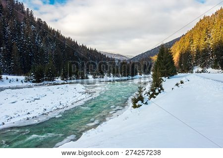 Mountain River In Winter. Snow Covered River Banks. Forest In Snow On The Distant Mountain. Cloudy M