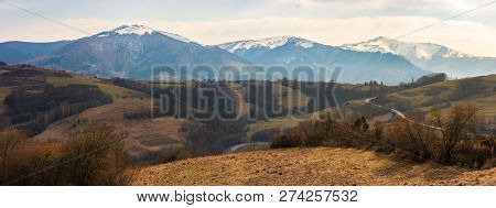 Early Springtime In Mountains. Weathered Grass And Leafless Trees On The Rolling Hills. Peaks Of Hig