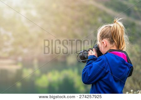 Cute Little Caucasian Girl Taking Photographs Of The Wildlife In The Park Outdoors