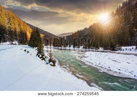 Mountain River In Winter At Sunset In Evening Light. Snow Covered River Banks. Forest In Snow On The