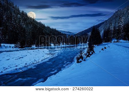 Mountain River In Winter At Night In Full Moon Light. Snow Covered River Banks. Forest In Snow On Th