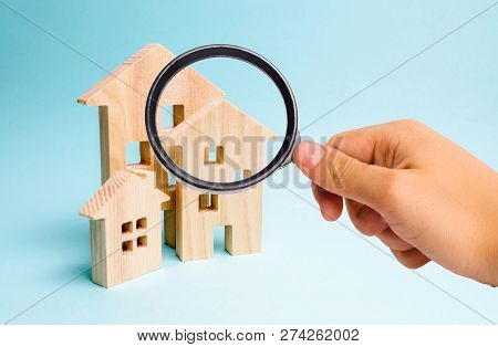 Magnifying Glass Is Looking At The Three Houses. Buying And Selling Of Real Estate, Construction. Ap