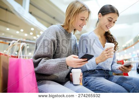 Cute shoppers with drinks and smartphones scrolling through notifications during break after shopping