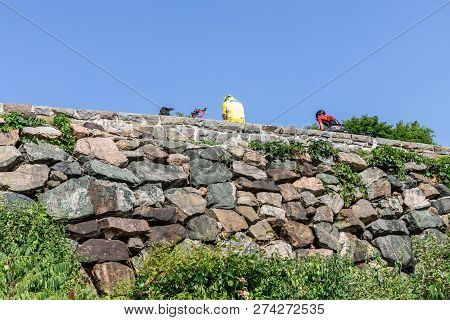 Gatineau, Quebec - July 7, 2018 - Horizontal, Looking Up At Two Cyclists Resting On The Stone Wall O