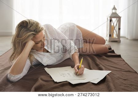 Beautiful Blonde Woman Lays On Floor, And Draw Design Skeches By Hand.