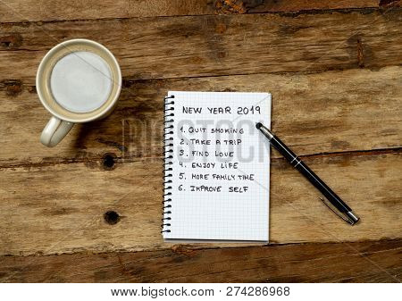 2019 New Year Resolutions Written On Notebook With Pen And Coffee On Wood Table In Happy Life Goals