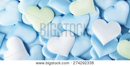 Valentine's Day hearts Background. Holiday Abstract Valentine Background with blue, green and white pastel colors satin Hearts. Heart backdrop. Love concept, wedding. Flat lay, top view