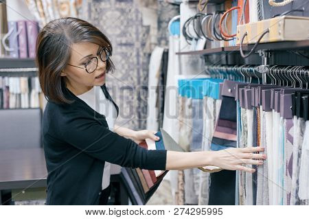 Fabrics Store, Adult Female Looking And Touching Samples, Female Designer Chooses Fabrics For Interi