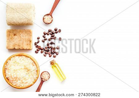Aromatherapy And Spa Concept. Spa Salt With Coffee Scent Near Soap, Spa Oil And Loofah On White Back