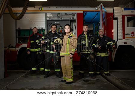 Photo of four male and female firefighters on background of fire truck