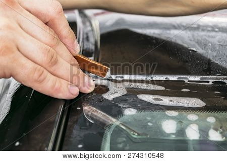 Car Wrapping Specialist Cutting Vinyl Foil Or Film On Car. Protective Film On The Car. Applying A Pr