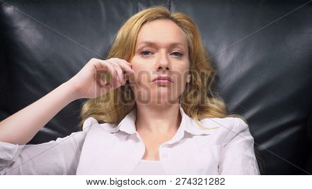 Close-up. An Elegant Woman In A White Suit Sits In A Large Black Leather Chair. The Woman Is Bored A