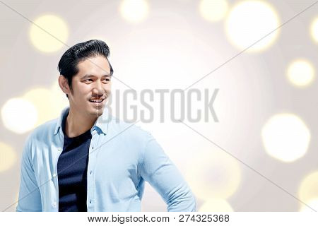 Handsome Asian Man With Blue Shirt Standing Against Bokeh Lights Background. Valentines Day