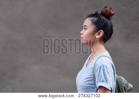 Asian Woman Standing Sideways In Front Of A Wall
