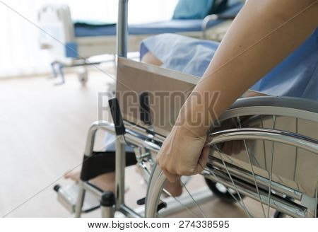 Close Up Of Hand Patient Using Wheelchair In Hospital