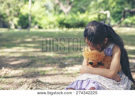 Sad Child With Family Problem,hugging Teddy Bear On Wooden Swing In Park.asian Little Girl Sitting W