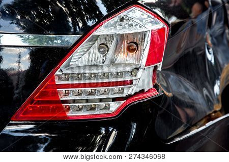 A Rear Lamp Damaged In The Incident And A Fender Of A Car, A Close-up Rear Light Of A Black Car.