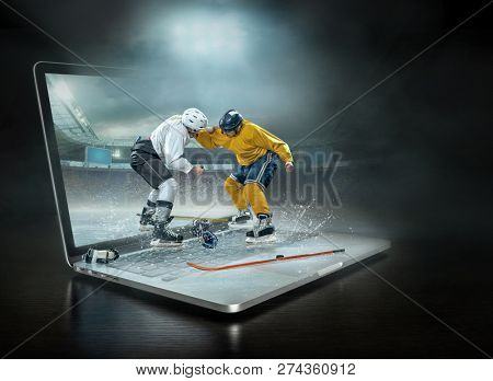 Caucassian ice hockey Players in dynamic boxing action in a professional sport game play on the laptop in hockey under stadium lights.