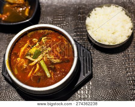 korean cuisine - top view of yukgaejang (hot and spicy soup with beef, eggs, mushrooms, starch noodles, scallions, ferns, bean sprouts, served with boiled rice) in metal bowl in local restaurant poster