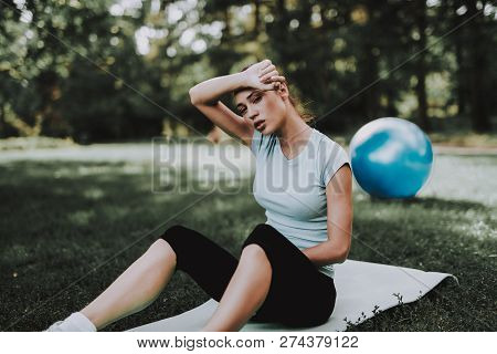 Woman In Sportswear After Yoga Exercises In Park. Sport And Healthcare Concept. Sitting Young Woman.