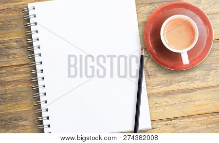 Notepad Or Notebook With Pencil And Cup Of Coffee On Brown Wood Table Background.using Wallpaper For