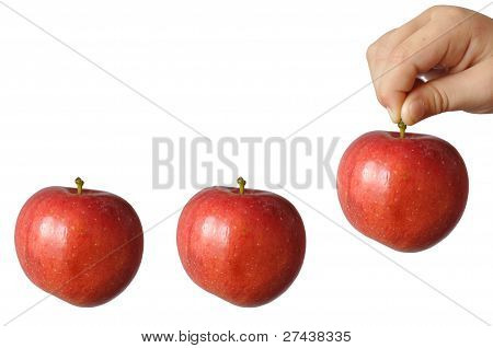 A child holds a large red apple fruit stem