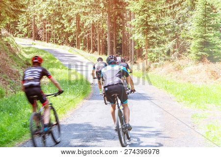Ukraine, Vinnitsa, July 17, 2028. Cyclists Ride On Asphalt Road In The Forest, Cycling Competitions,