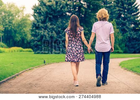 Back View Of Couple Walking In Beautiful Park During Summer Weather Holding Hands Together.