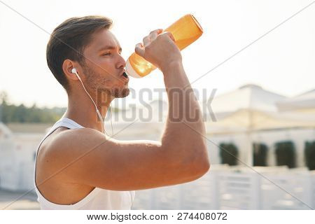 Sports Concept. Man Drinking Water After Running Workout At Beach. Portrait Of Thirsty Healthy Athletic Male With Fit Body Drinking Refreshing Drink, Resting After Running Or Training Outdoor. poster