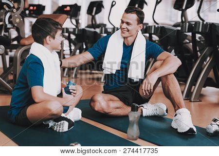 Young Father And Son Sitting On Mats In Sport Club. Healthy Lifestyle Concept. Sport And Training Co