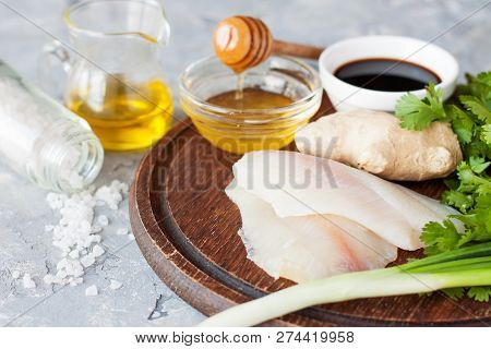 Raw Tilapia Filet, Ginger, Honey, Green Onion, Parsley, Soy, Sauce And Condiments On Wooden Cutting