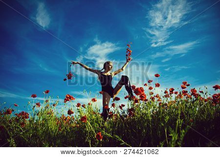 drug and love intoxication, girl jump with long curly hair in black bodysuit in red flower field of poppy seed with green stem on blue sky background, summer, drug and love intoxication, opium poster