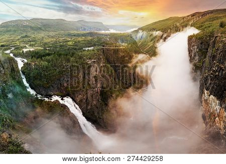Beautiful View Of Waterfall. Summer Landscape In The Mountains With A Waterfall And Fog. Foggy Weath
