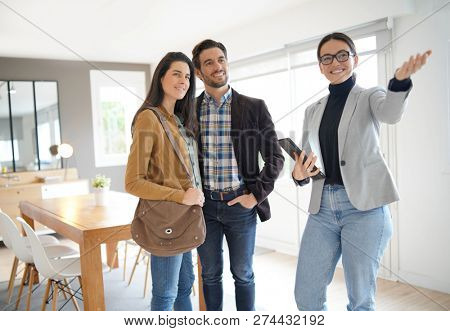 Real estate agent showing modern house to attractive couple