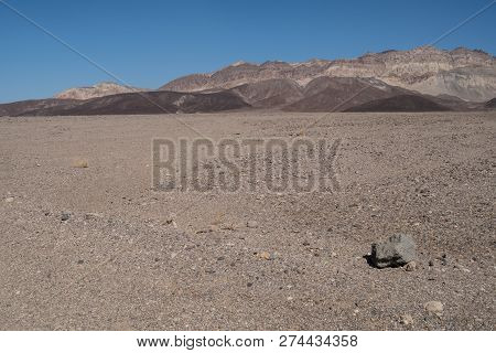 A Lone Rock On The Dirt And Sand In Death Valley National Park, With The Panamint Mountain Range In