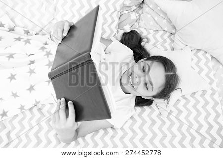 Girl child lay bed read book top view. Encourage useful habits.Kid prepare to go to bed. Pleasant time in cozy bedroom. Girl kid long hair cute pajamas relax and read book. Satisfied with happy end. poster