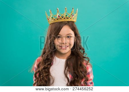 Kid Wear Golden Crown Symbol Of Princess. Girl Cute Baby Wear Crown While Stand Blue Background. Bec