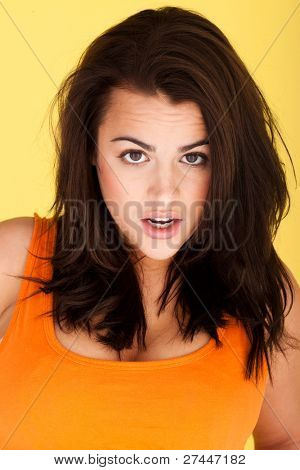 Beautiful Woman With Shocked Expression, beautiful woman with mussed hair and wide eyed shocked expression isolated on yellow.