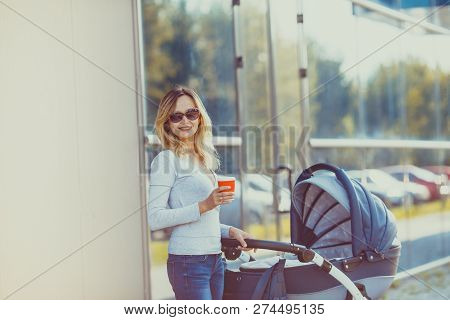 Trendy Mother Posing With Cup Of Coffee And Pram