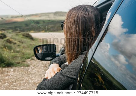 A Girl Driver Or A Female Traveler Inside The Car Looks Out The Window To The Road Ahead Or Unknown
