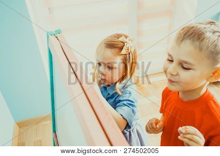 Top View Of Boy And Girl Drawing On A Chalkboard
