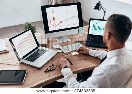 Analyzing Sales Pitch. Top View Of Young Businessman In Formalwear Analyzing Data Using Computer Whi