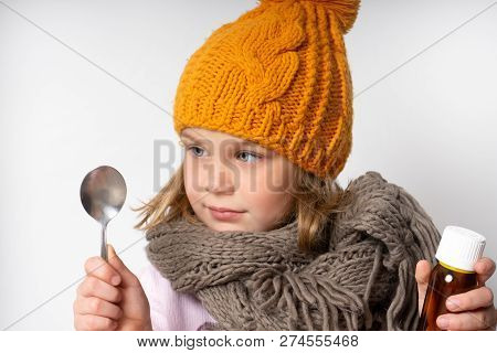 Little Woolen Dress In A Warm Scarf And Knitted Hat. Holds In His Hands A Bottle Of Cough Syrup For