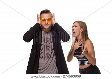 Angry Blonde Young European Woman Gestures With Hands, Shouts At Husband Who Is Guilty, Stands Toget