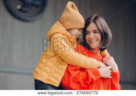 Photo Of Positive Lovely Mother And Small Child Embrace Friendly, Have Good Relationships, Demonstra