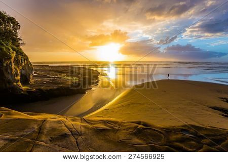 Phenomenal beautiful sunset on the beach near Auckland. Coast of the North Island of New Zealand. Concept of active and ecological tourism