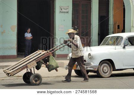Granma, Cuba-april 04,2016 : Streetlife At Cuba. Man Pushing A Push Car And A Parkled Old American C