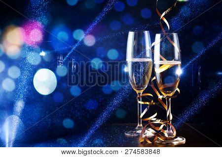 two glasses of champagne in the spotlight - new year celebration
