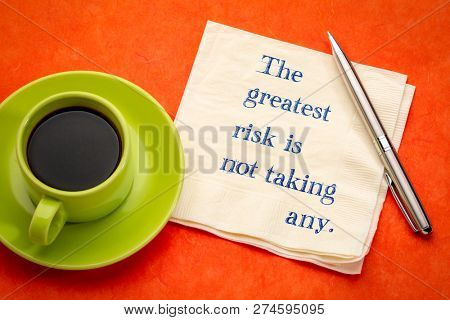 The greatest risk is not taking any - handwriting on a napkin with a cup of coffee